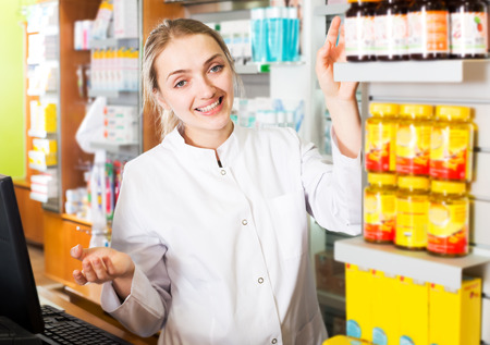 farmacy: Portrait of happy young female pharmaceutist working in modern farmacy Stock Photo