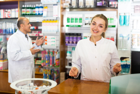 farmacy: Positive senior pharmacist and female young assistant working at farmacy reception Stock Photo