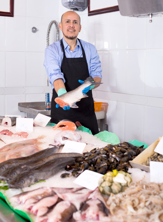 frozen fish: Senior man selling frozen fish and seafood in store Stock Photo