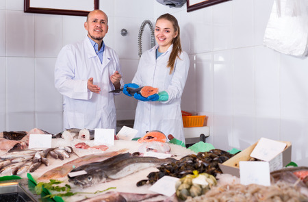shopgirl: Cheerful shopgirl and salesman posing near display with cooled fish