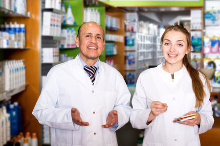 farmacy: Pharmacist and pharmacy technician posing in modern farmacy