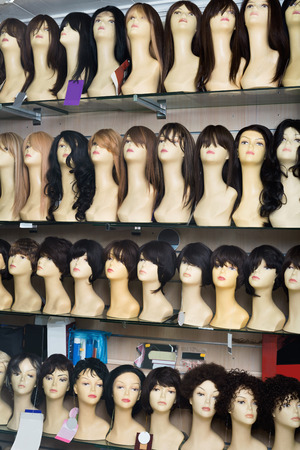 peruke: Mannequins with different style wigs on shelves of hair salon Stock Photo