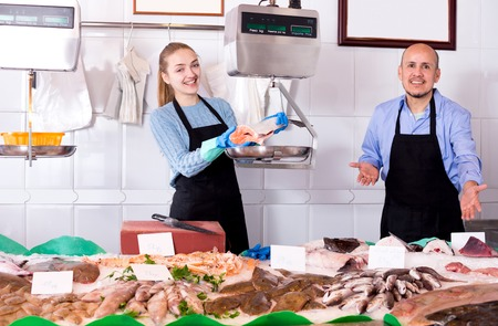 cooled: Young assistant offering cooled fish in shop with friendly seller