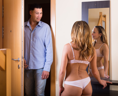 coming home: Long-haired woman in sexy lingerie and boyfriend coming home Stock Photo