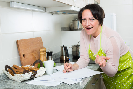 householder: Happy brunette woman applying for bank loan at kitchen