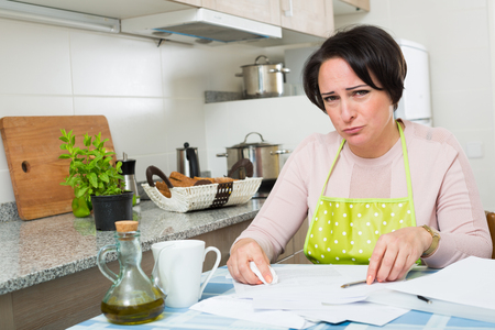 downcast: Middle aged miserable woman with financial documents at kitchen table Stock Photo