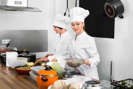 diligente: Glad diligentes mujeres chefs que preparan el alimento en cocina del restaurante Foto de archivo