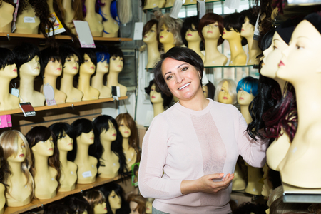 peruke: Positive brunette female looking at periwigs in shop and smiling