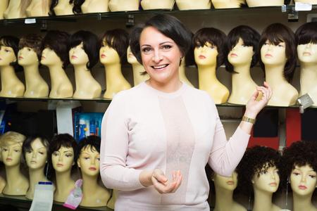 peruke: Curious female customer selecting natural hair wig in store Stock Photo