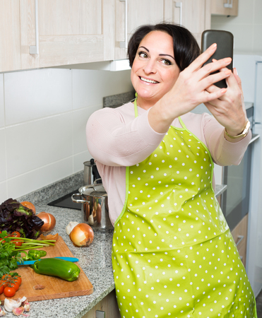 kitchen spanish: Portrait of smiling spanish  housewife in apron making selfie in domestic kitchen
