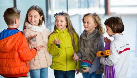 junior school: Street portrait of  happy junior school girls and boys talking Stock Photo