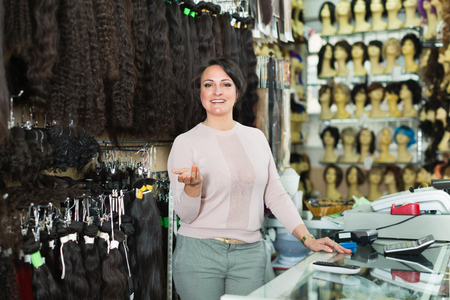 chignon: Shop friendly smiling woman posing at counter with artificial and natural hair Stock Photo