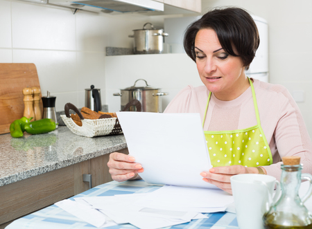 householder: Positive woman sitting at kitchen table with financial documents