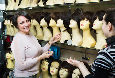 purchasers: Ordinary women buying modern periwigs and smiling in a shop Stock Photo