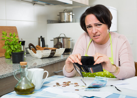 miserable: Miserable housewife sitting with bills and money in kitchen
