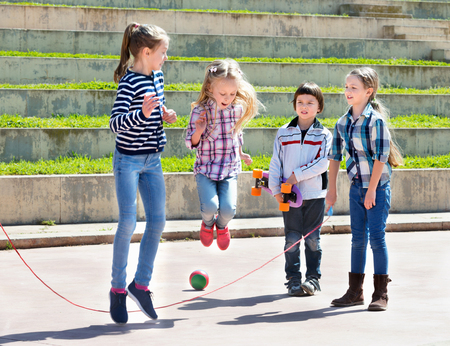 Positive children playing skipping rope jumping game and laughing outdoors