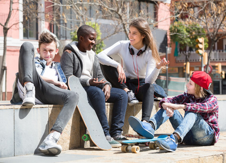 blabbing: Happy young  people spending time together and talking in sunny day Stock Photo