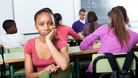social outcast: Outcasted young student being mobbed by other students in the class Stock Photo