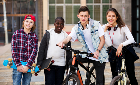 blabbing: Happy four teenagers with skateboards posing in town square Stock Photo