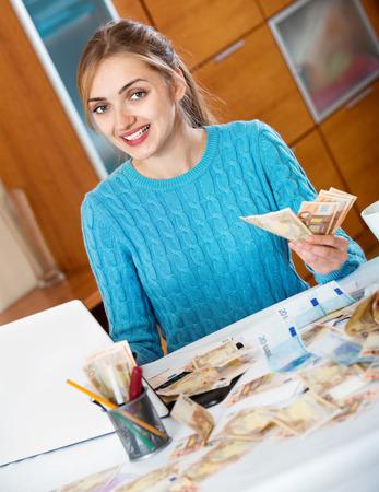 ganancias: Hermosa mujer sonriente ganar dinero en casa siendo independiente