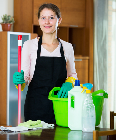 dusting: american maid in apron dusting and wiping in residential property