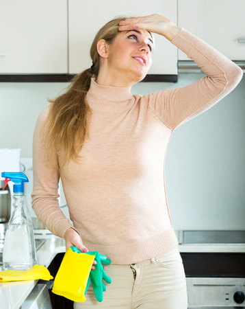 Portrait tired young woman in rubber gloves posing at kitchen Stock Photo