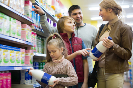 pasteurized: Happy family buying pasteurized milk in supermarket together