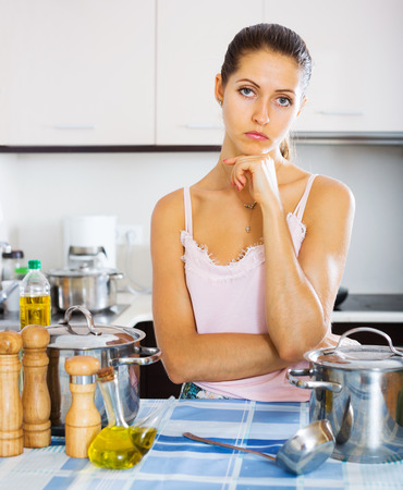 dispirited: Sad young woman standing at kitchen table