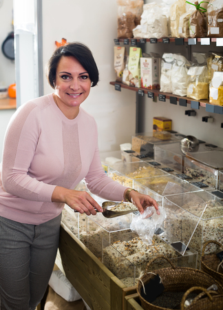 mature brunette: Smiling mature brunette woman 40s choosing cereals sold by weight in organic shop Stock Photo