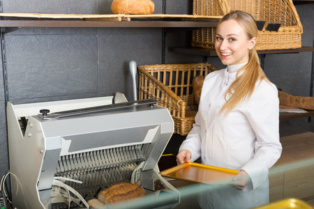 automatically: Cheerful young girl dressed as baker showing automatically cut bread in the bakery