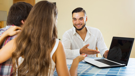 cheerfully: Couple and young salesman talking cheerfully about purchase at home Stock Photo