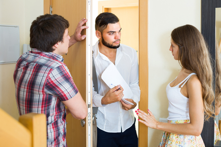 repayment: Banker clamouring credit repayment from young couple at the doorway Stock Photo