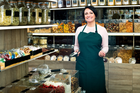 candied fruits: Happy mature brunette woman wearing apron and selling nuts and dried fruits in organic shop