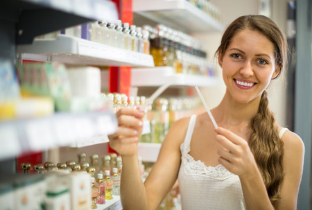 vend: Attractive smiling girl in a good mood choosing perfume in the store Stock Photo