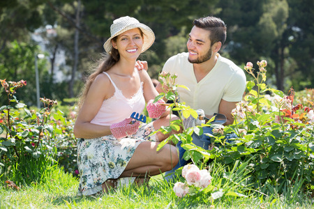 floriculturist: Smiling family in gloves planting plants in garden Stock Photo