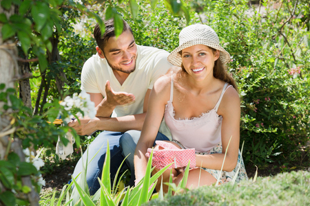 floriculturist: Young family seedling garden flowers grower in summer holiday Stock Photo