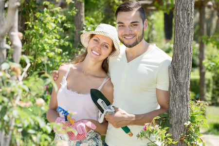 floriculturist: Cheerful married couple in garden smiling at summer vacation