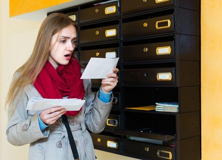 Geschokte vrouw die zich met brief dichtbij brievenbus bevindt