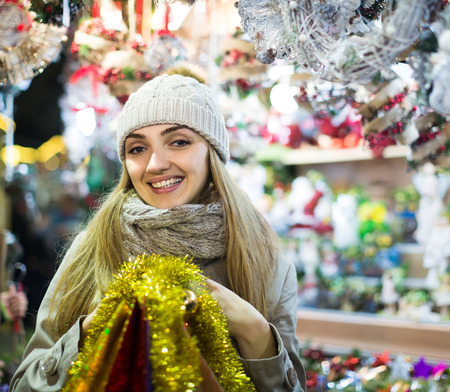 spanish woman: Smiling spanish woman shopping at Christmas fair before Xmas in evening time Stock Photo