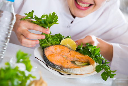 corcovado: Positive female chef posing with trout fillet in kitchen
