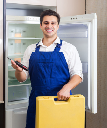 refrigerator kitchen: Smiling adult handyman repairing refrigerator in domestic kitchen