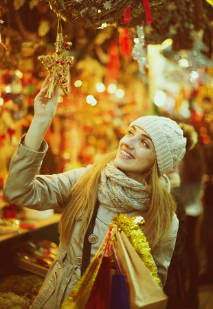 lifestile: Portrait of smiling longhaired girl near counter with Christmas gifts in evening time