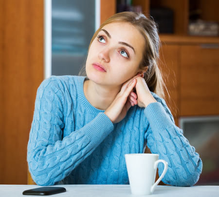 downcast: Sad young woman waiting for a phone call in domestic interior Stock Photo