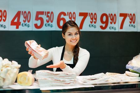 salo: Portrait of smiling female seller offering salo and lard in butchery Stock Photo