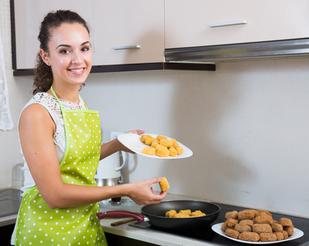 crocchette: woman rolling filled croquettes at kitchen table Stock Photo