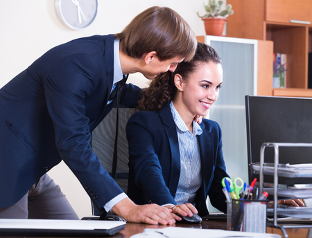 subordinate: Boss touching subordinate employee in office