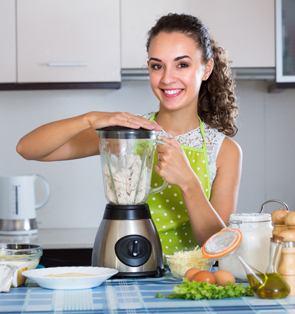 liquidiser: Happy young brunette woman making croquettes using blender at home