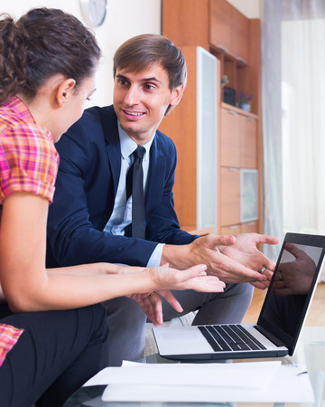 conduction: Banking happy russian agent with nice offer consulting customer indoors Stock Photo