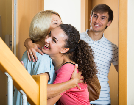 Happy mature mother meets son with his wife at doorway Stock Photo