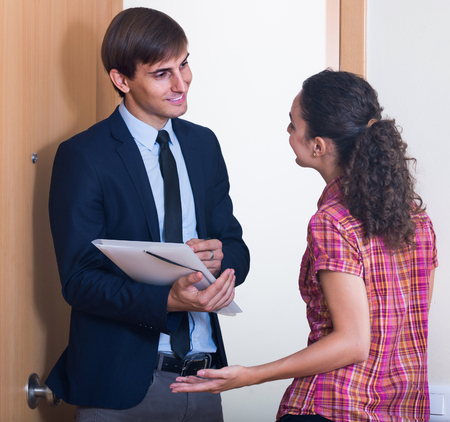 householder: commercial agent greeting householder and selling subscriptions in hall Stock Photo